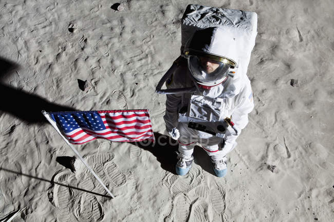 An astronaut on the surface of the moon next to an American flag — Stock Photo
