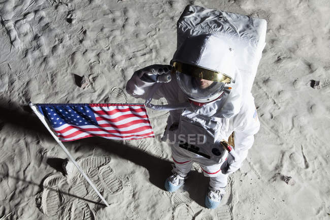 An astronaut on the surface of the moon saluting an American flag — Stock Photo