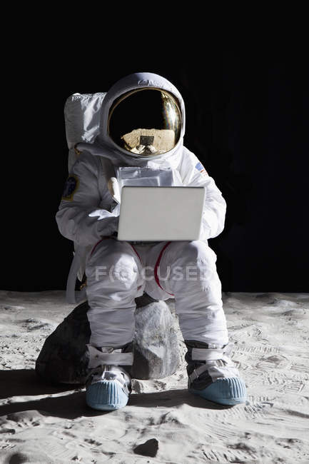 Astronaut sitting on rock on moon and using laptop — Stock Photo