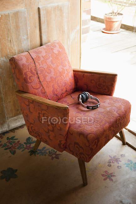 Headphones on shabby vintage armchair — Stock Photo