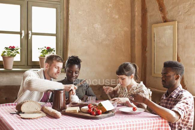 Dos parejas que tienen comida rústica simple juntos - foto de stock