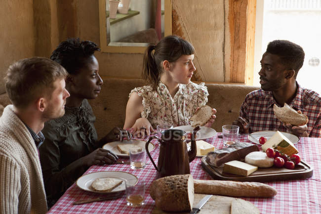 Two couples having simple rustic meal together and talking — Stock Photo