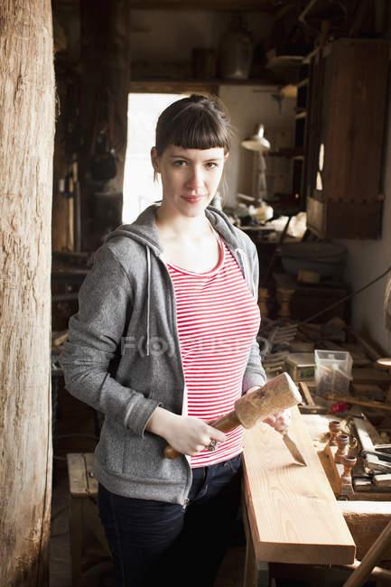 Портрет Жінка тримає зубилом і молотком в майстерні — стокове фото