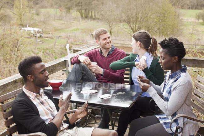 Dos parejas felices jugando cartas al aire libre - foto de stock