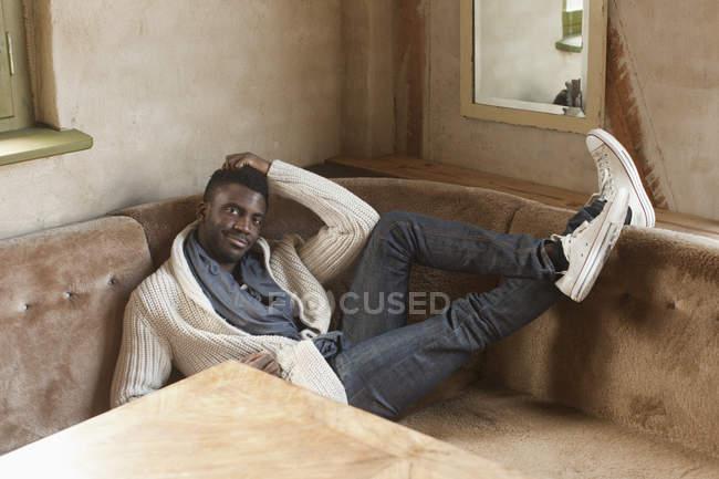 Portrait d'un homme élégant allongé sur un canapé dans une cabine — Photo de stock