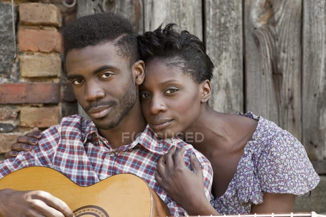 Retrato de jovem casal afetuoso sentado na frente da parede de madeira com guitarra — Fotografia de Stock