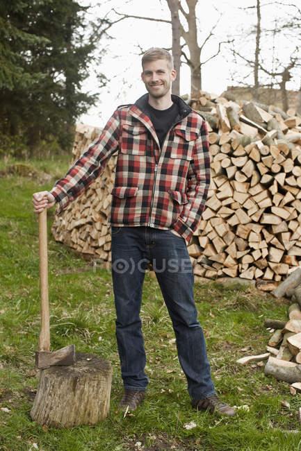 Portrait d'un homme tenant une hache debout devant une pile de bois — Photo de stock