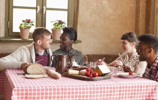 Dos parejas que tienen comida rústica simple juntos y hablando - foto de stock
