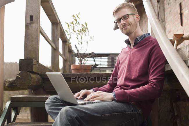 Porträt eines Mannes mit Laptop auf Holztreppe — Stockfoto