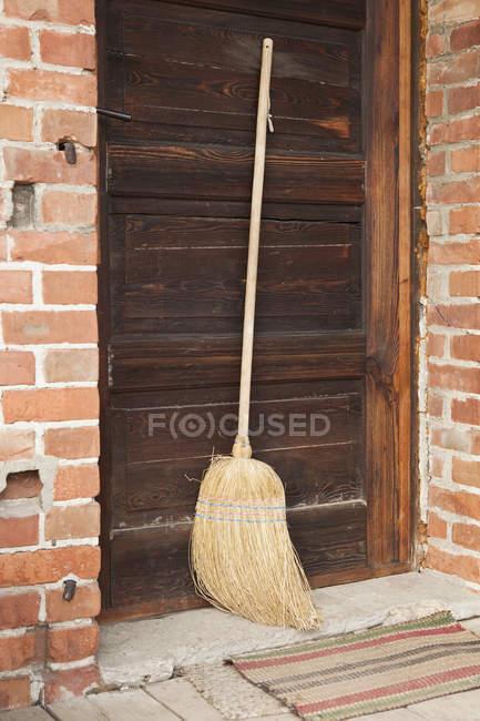 Rural broom leaning against wooden door — Stock Photo
