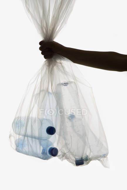 Crop hand holding transparent garbage bag of plastic bottles — Stock Photo