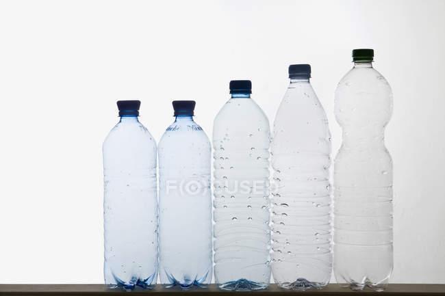 Row of empty plastic water bottles on white — Stock Photo