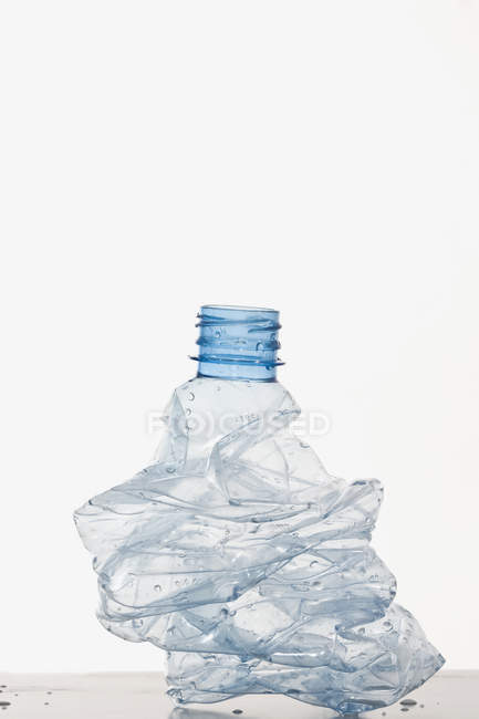 Crumpled plastic water bottle over white — Stock Photo