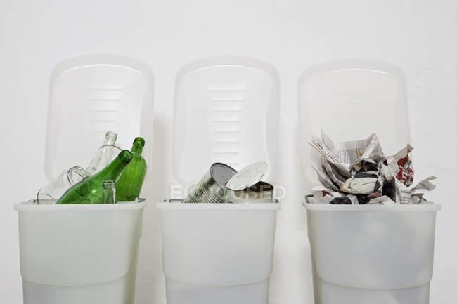 Trois bacs de recyclage remplis d'ordures triées — Photo de stock