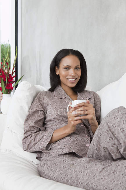 Portrait of young woman relaxing in the morning with cup of coffee — Stock Photo