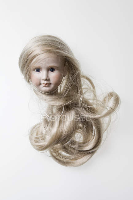 Head of porcelain doll with long blond hair — Stock Photo