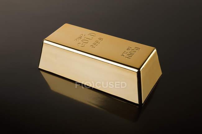 Золото-бар на отражающей поверхности черный — стоковое фото
