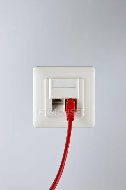 Câble réseau rouge branché sur prise murale — Photo de stock