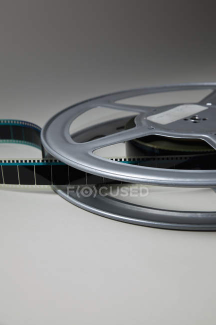 Spool of film on reel at grey backdrop — Stock Photo