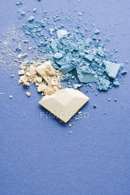 Crushed blue and beige eye shadow on blue backdrop — Stock Photo