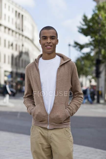 Ritratto di giovane in piedi in città con le mani in tasca — Foto stock