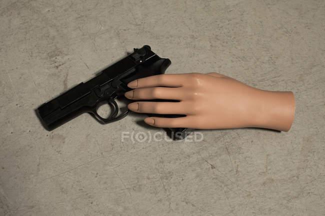 Mannequin hand and handgun on beige surface — Stock Photo
