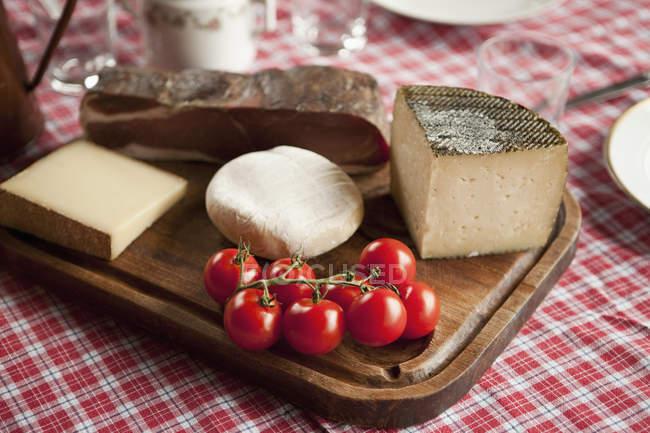 Натюрморт сыра и помидоров на резка дерева доска — стоковое фото