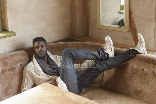 Portrait of stylish man reclining on sofa in booth — Stock Photo