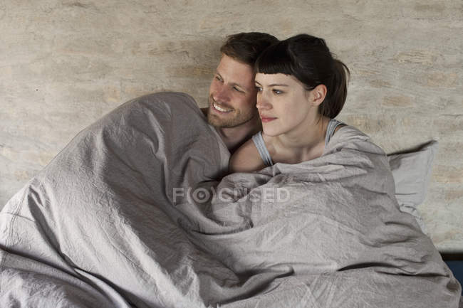 Romantic couple snuggling in bed and looking away — Stock Photo