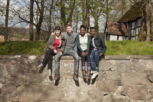 Quatre amis assis sur un mur de pierre à la campagne — Photo de stock