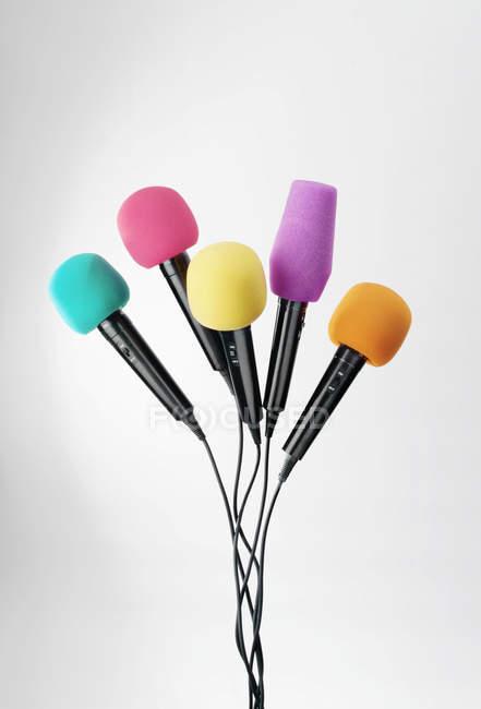 Различные цветные микрофоны на сером фоне — стоковое фото