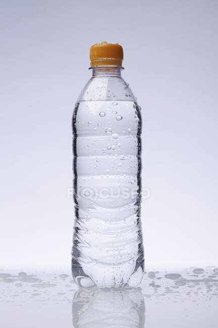 Garrafa de plástico com água no fundo claro — Fotografia de Stock