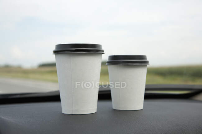 Two disposable coffee cups in car — Stock Photo