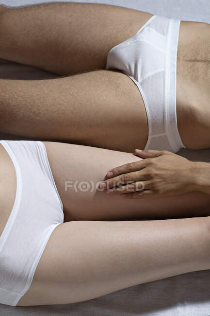 Imagen recortada de mujer y hombre con ropa interior blanca - foto de stock