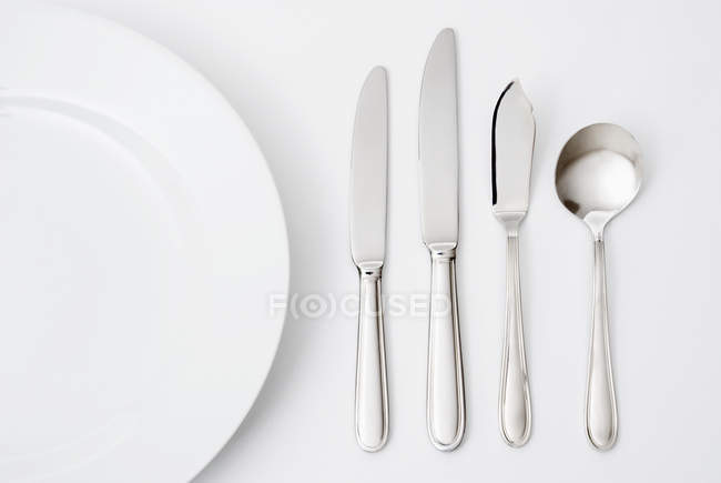 Different cutlery and kitchen utensils on grey surface — Stock Photo