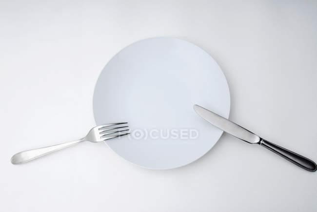 Diferentes utensílios de cutelaria e cozinha na superfície cinza — Fotografia de Stock