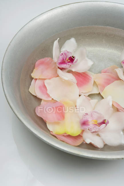 Crop bowl of water with flower petals — Stock Photo