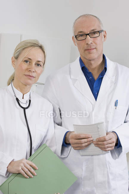 Portrait of dentist and dental assistant standing in clinic — Stock Photo