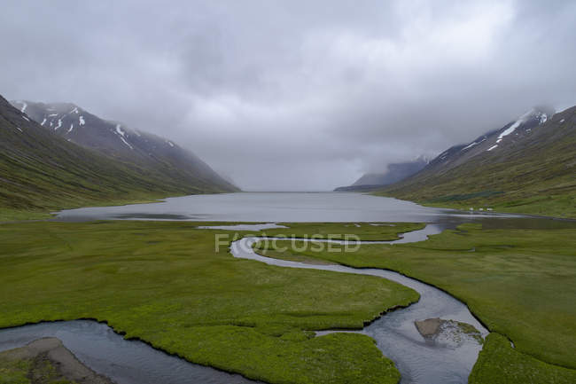 Serene landscape of lake at mountain valley under cloudy sky — Stock Photo