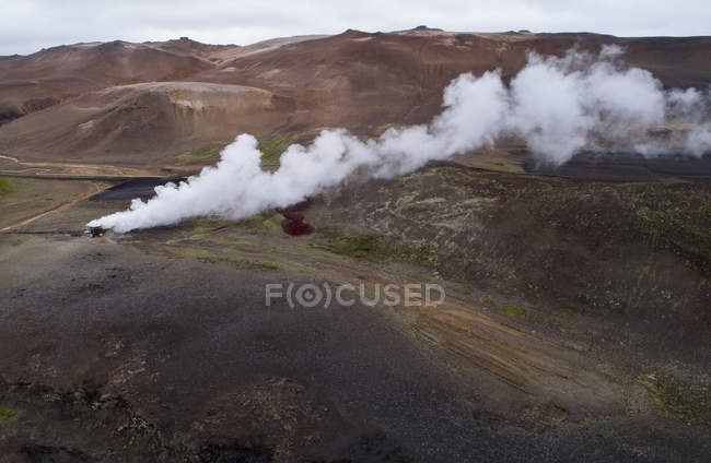 Drone view of rusty containers emitting smoke on barren landscape — Stock Photo