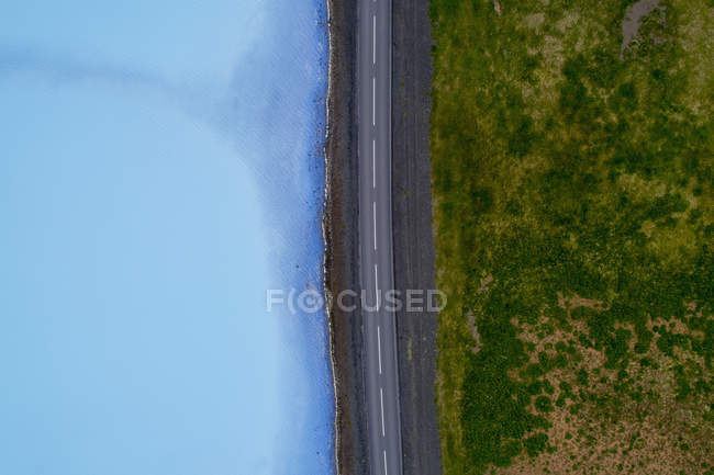 Directly above view of road amidst field and turquoise water — Stock Photo
