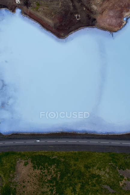 Drone view of vehicle driving on road by turquoise lake — Stock Photo