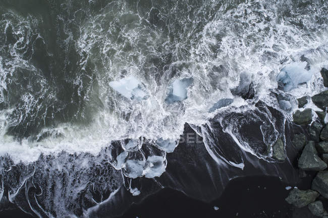 Drone view of ice pieces in surfing wave — Stock Photo