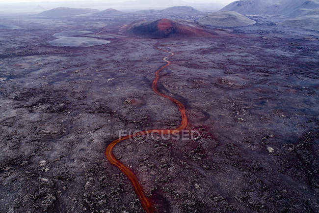 Fluxo de vulcão e lava fluindo através da paisagem árida, — Fotografia de Stock