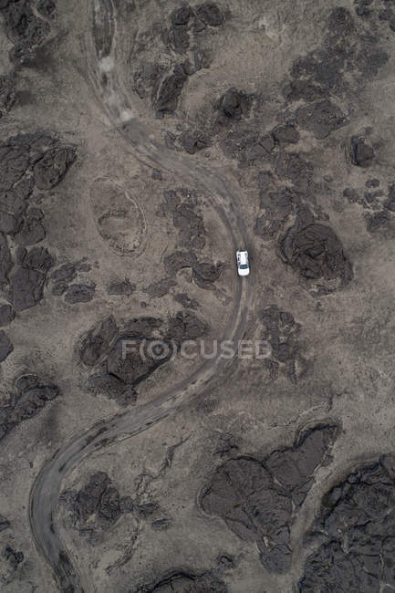 Aerial view of vehicle driving on dirt road over barren landscape, — Stock Photo
