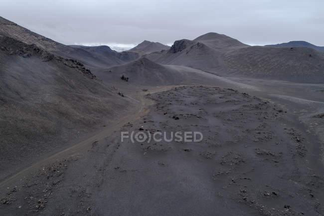 Мальовничим видом горбистий ландшафт проти хмарного неба — стокове фото