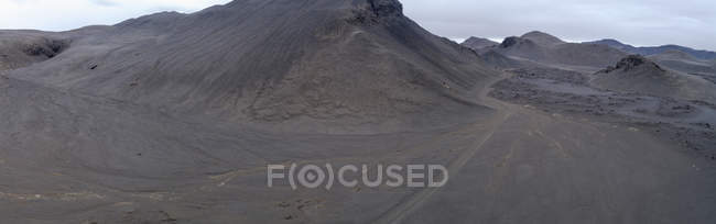 Panoramic view of volcanic terrain landscape against sky, — Stock Photo