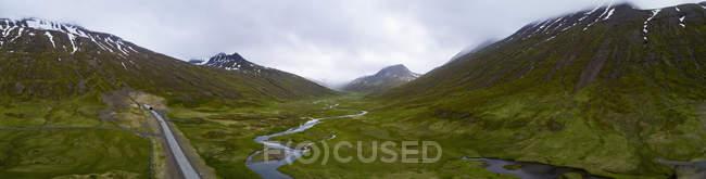 Vista panorâmica da estrada por córrego no vale verde da montanha — Fotografia de Stock