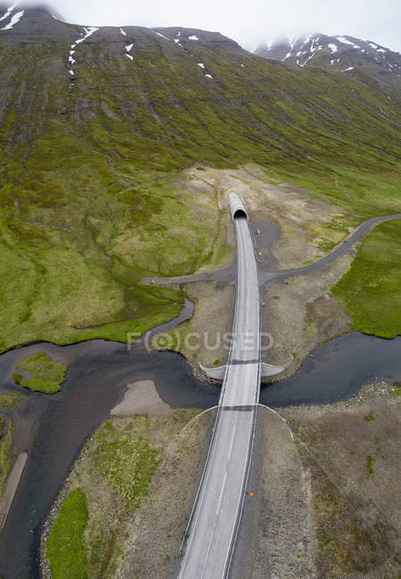 Drone view of empty road over stream at mountain valley — Stock Photo