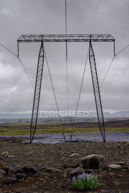 Electricity pylons placed on field against cloudy sky — Stock Photo